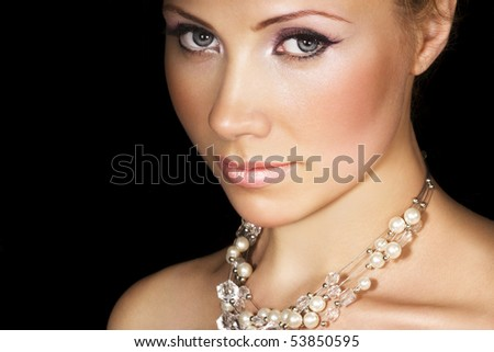 Beauty with pearl necklace on black. Space for text.