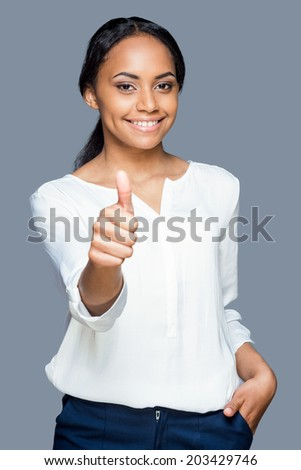 Beauty with thumb up. Waist up of attractive young African woman showing her thumb up and smiling while standing against grey background