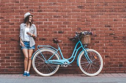 Beauty with vintage bike. Beautiful young smiling woman standing near her vintage bicycle with basket full of flowers while she leans against the wall.