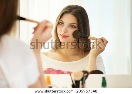 Beauty woman applying makeup. Beautiful girl looking in the mirror and applying cosmetic with a big brush. Girl gets blush on the cheekbones. Powder, rouge  #205957348