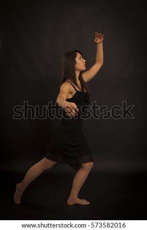Beauty woman dancing in a dark room. Red smoke and black background