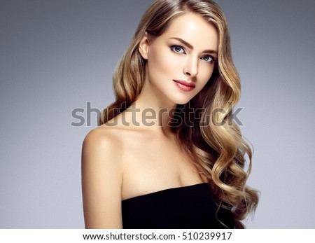 Beauty Woman face Portrait. Beautiful Spa model Girl with Perfect Fresh Clean Skin. Blonde female looking at camera and smiling on gray background. Beautiful hairstyle Youth and Skin Care Concept
