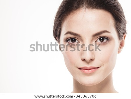 Beauty Woman face Portrait. Beautiful Spa model Girl with Perfect Fresh Clean Skin. Brunette female looking at camera and smiling. Youth and Skin Care Concept. Isolated white background
