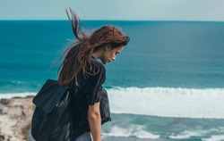 Beauty woman hipster portrait, outdoor fashion model, jeans denim, t shirt, backpack, Bali, backpack hipster, ocean beach, sea view, wild hair, amazing photo, sad moods, waves, crazy girl