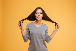 Beauty woman holding to the hair. isolated orange background