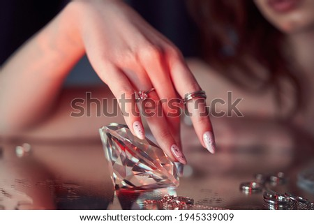 Beauty Woman holds big diamond in hand while lying on table. Beautiful hands, professional manicure, large diamond brilliant