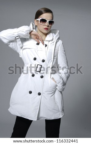 beauty woman in a fashionable white coat dress in sunglasses posing background