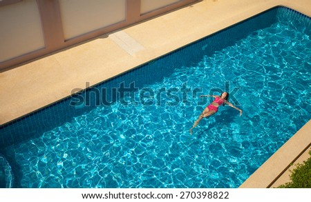 Beauty Woman In Red Swimming Suit Swimming and Relaxing In Big Blue \Pool. Top view.