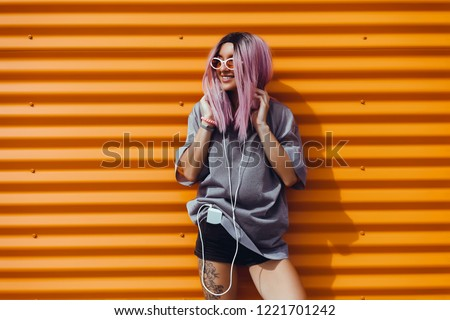 Beauty woman listening music on headphones, outdoor hipster portrait, purple hair, fashion model, color, sunglasses, smartphone, tattoo, sunglasses, orange wall, happy face, smile, hipster style