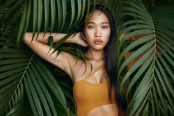 Beauty. Woman model with long straight hair and palm leaves. Asian girl with beautiful exotic face at tropical nature