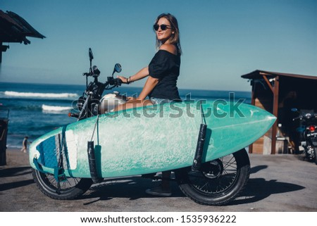 Beauty woman using custom old motorcycle, outdoor hipster portrait,surfboard,brutal girl, sunglasses, hipsters in stylish clothing for a retro motorcycle on the street,beach, surfboard, longboard,Bali #1535936222