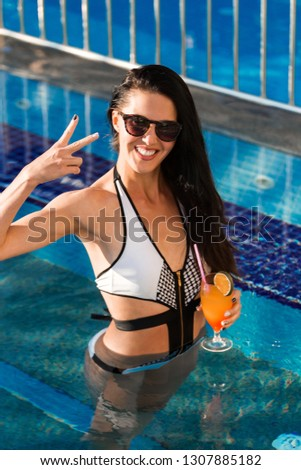 beauty woman with long black hair and perfect slim body standing in the blue swimming pool holding a cocktail. Woman wearing white swimwear and sunglasses. concept of happy holiday and fun party