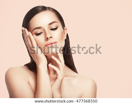 Beauty Woman with perfect healthy skin Portrait. Beautiful Brunette Girl touching her face and smiling Spa model, pampering her skin. Beige background
