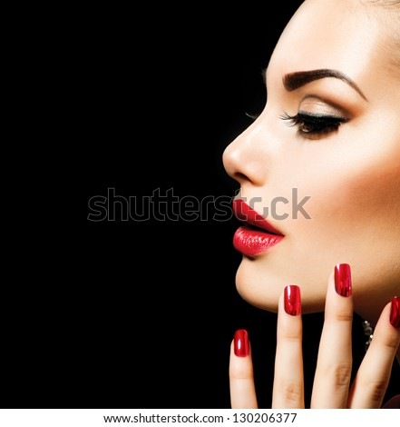 Beauty Woman with Perfect Makeup. Beautiful Professional Holiday Make-up. Red Lips and Nails. Beauty Girl\'s Face isolated on Black background. Glamorous Woman