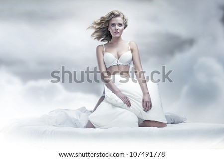 Beauty woman with pillow over sky background
