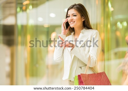 Beauty woman with shopping bags in shopping mall is talking by phone. Sales. Shopping Center.