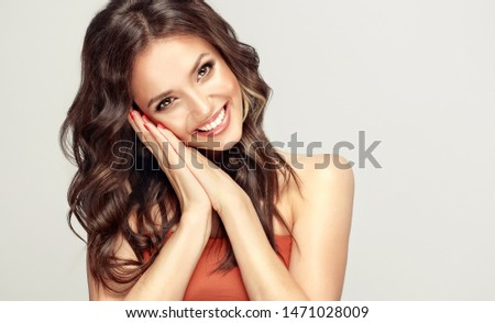 Beauty woman with smile surprise holds cheeks by hand .Beautiful girl  with curly hair laugh sincerely. Presenting your product. Expressive facial expressions . Happy people .  #1471028009