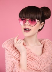 Beauty wow. Fashion surprise teen girl model. Brunette in heart sunglasses with matte lips and bun hairstyle in knitted sweater posing over studio pink background.