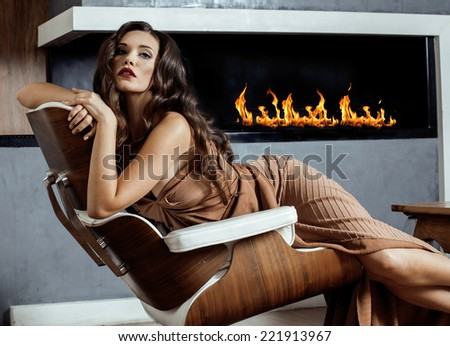 beauty yong brunette woman sitting near fireplace at home, winter warm evening in interior