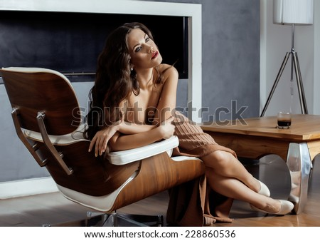 beauty yong brunette woman sitting near fireplace at home, winter warm evening in interior dreaming