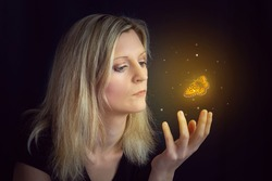 Beauty young blond hair woman hold hand under glowing orange butterfly. Photomanipulation glowing lepidopteran on black background