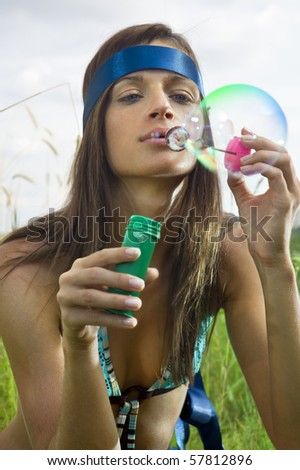 beauty young woman blowing soap bubbles in summer day