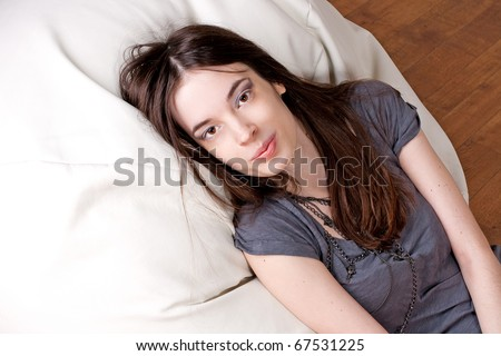 beauty young woman with brown eyes lies on a pillow