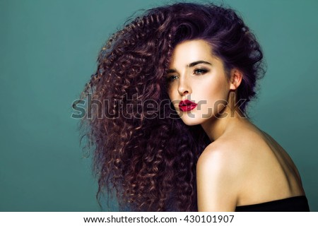 Beauty young woman with curly big and long hair. Permed hair. Glamour lady, Beauty Girl on blue background. Beautiful Woman Portrait. redhead Wavy Hair, perfect make up, red lips, thick eyelashes.