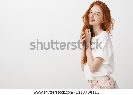 Beauty, youth, and hairdressing concept. Charming and playful redhead female with long beautiful hair and natural color, smiling tenderly at camera, playing with strands, posing over gray wall