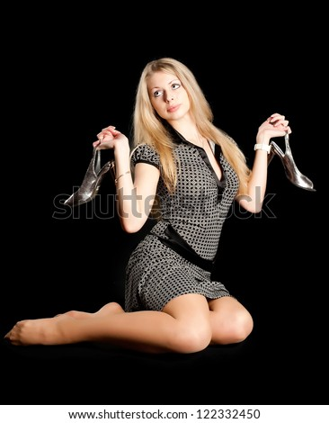 Beautyiful woman sitting on floot with shoes in hands