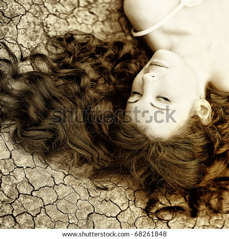 Beauutiful young woman with long hair on the dried up ground