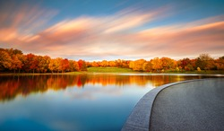 Beaver Lake / Lac Aux Castors in Montreal, Quebec, Canada with Peak Fall Colors and a Vibrant Sunset. The blue sky with streaking, colorful clouds are reflected into the perfectly still lake.