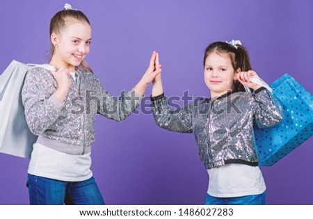 Because image is everything. Girls sisters friends with shopping bags violet background. Shopping and purchase. Black friday. Sale and discount. Shopping day. Children bunch packages. Kids fashion.