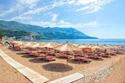 Becici beach in Montenegro , Sun umbrellas and loungers at the sandy beach . Summer Adriatic seaside