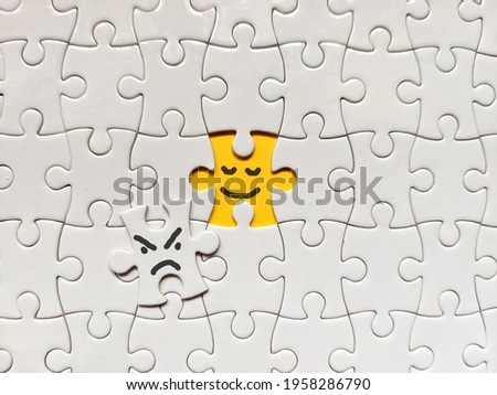 Becoming a better person concept using puzzle. Smiling and good yellow puzzle over bad and angry white puzzle in the middle of frame. Suitable for positivity, becoming better person, patience concept. Stock foto ©