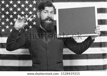 Becoming a master barber. Barber teaching barbering on american flag background. Bearded barber holding scissors and blackboard in class. Barber education and career, copy space.