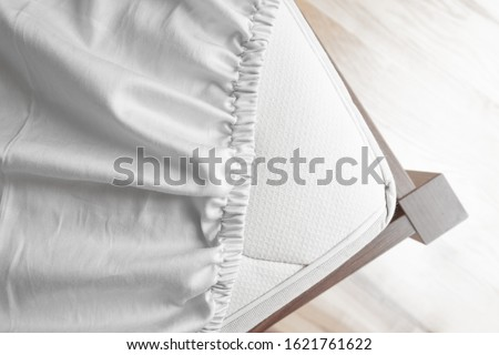 Photo of  Bed corner with white fitted sheet. White sheet with elastic band. Bed cover.