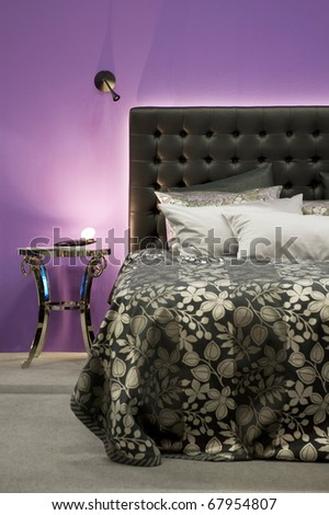 Bed in front of a purple wall