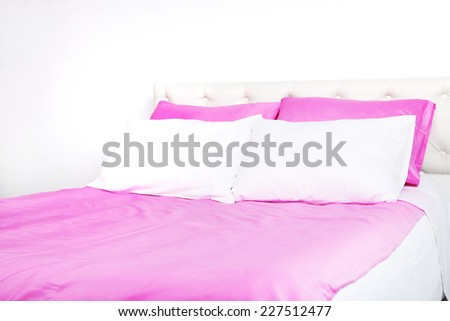 Bed in pink bed linen in room