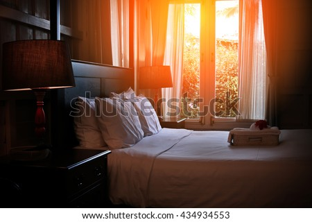 Bed maid-up with clean white pillows and bed sheets in beauty room. Close-up. Lens flair in sunlight. Sunrise garden view on the background