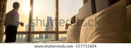 Bed maid-up with white pillows and bed sheets in cozy room. Businessman with cup of coffee standing at window. Focus on cushion. Horizontal photo banner for website header design. Business concept #557715604