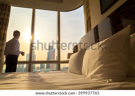 Bed maid-up with white pillows and bed sheets in cozy room. Young businessman with cup of coffee standing at window looking at city scenery on the background. Focus on cushion. Motivation concept #399937765