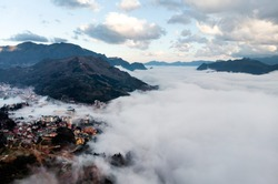 Bed of fog and clouds between the mountain valley in Sapa, Vietnam. Mountains among the clouds. Beautiful landscape with high mountains, blue sky and white clouds.