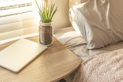 Bed Side Table Top with Laptop and Plant Work from Home Background