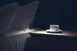 Bed side table with white mug against the bed at night time. Copy paste, nobody