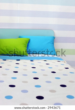 Bed with bright blue and green linen - home interiors