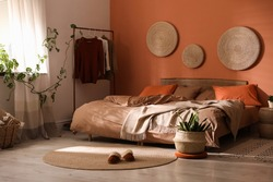 Bed with orange and brown linens in stylish room interior