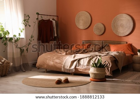 Bed with orange and brown linens in stylish room interior Foto stock ©