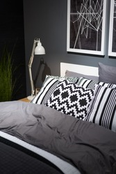 Bed with pillows in the bedroom near black wall. Interior in black and white colors