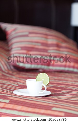 bed with two pillows, a cup of tea on the blanket